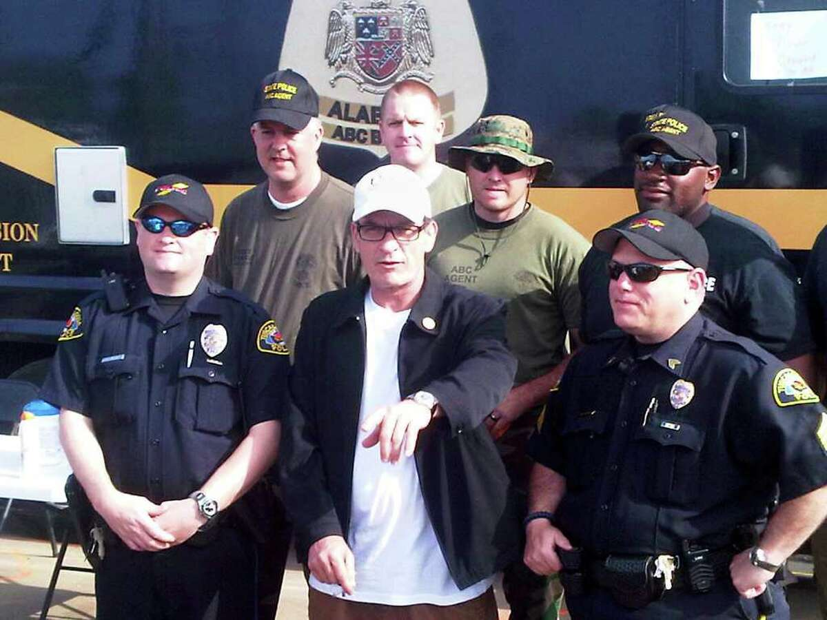 Actor Charlie Sheen poses with police officers and National Guard soldiers Monday, May 2, 2011, in Tuscaloosa, Ala. Sheen said Monday he is organizing a relief event for tornado victims in this Alabama town. (AP Photo/Alan Blinder)