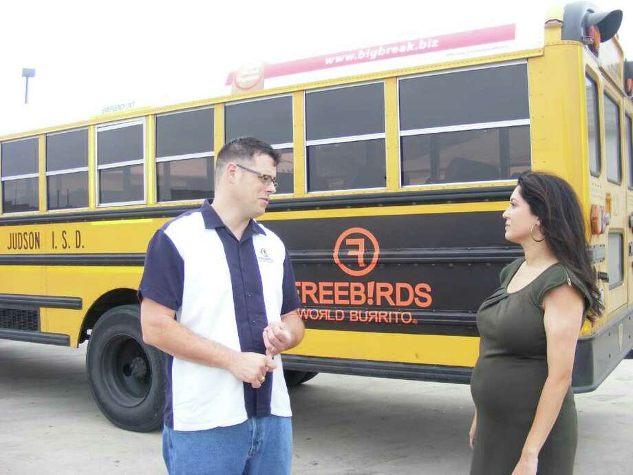 Pat Smiley, Freebirds district manager, talks with Yvette Reyna, executive director of the Judson Education Foundation, about his restaurant's advertisement that now graces the side of a Judson ISD bus. Photo: Photo By Jeff B. Flinn