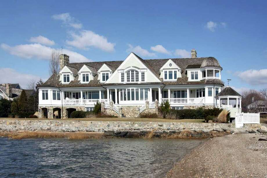 A waterfront house on Brush Island in Darien has all the amenities of living directly on L.I. Sound  –  private beach, water views from every room, a waterside gazebo and expansive terraces, along with an in ground pool  and a permit for a dock. The transitional Shingle-style house is both elegant and whimsical with Tuscan columns, coffered ceilings, display cabinets topped with seashell elements, an outdoor shower on the master-bedroom balcony and starfish knobs on the linen closet doors. The 11-room home on more than an acre has more than 6,400 square feet, with four bedrooms, four full baths, three half-baths and four fireplaces, one on a covered terrace. Photo: Contributed Photo / Stamford Advocate Contributed