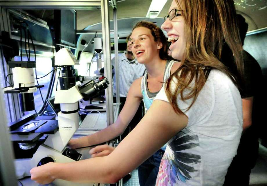 Leah May, 16, center, and Emily Meister, 16, right, hunt for eukaryotic cells during 10th-grade biology class on board the BioBus on Tuesday, May 3, 2011, at Columbia High in East Greenbush, N.Y. The BioBus, a mobile science classroom, allows students to use research-grade microscopes and video monitors. Regeneron Pharmaceuticals sponsored the BioBus and staff visit to Rensselaer County schools this week. (Cindy Schultz / Times Union) Photo: Cindy Schultz