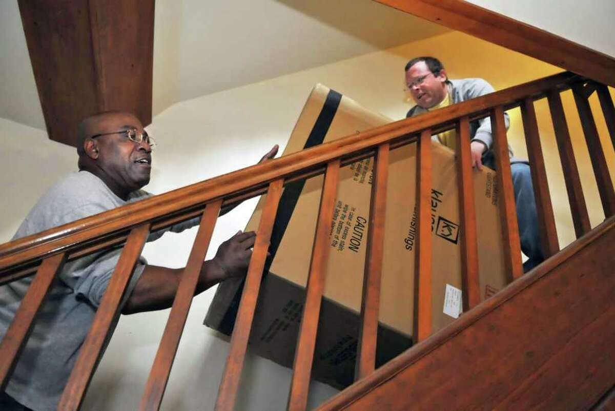 Addictions Care Center of Albany residents Bernie Waters, left, and Karl Oberacker carry new furniture donated by Rent-A-Center up to their apartment at the ACCA on Tuesday, May 3, 2011. (John Carl D'Annibale / Times Union)
