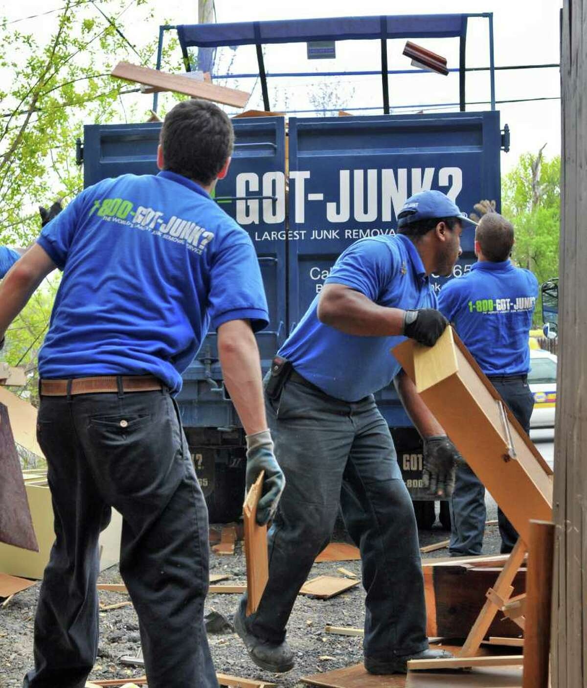 1-800-GOTJUNK workers remove old furnishings for the Addictions Care Center of Albany, making way for Rent-A-Center's donation of $15,000 worth of new furniture on Tuesday, May 3, 2011. (John Carl D'Annibale / Times Union)