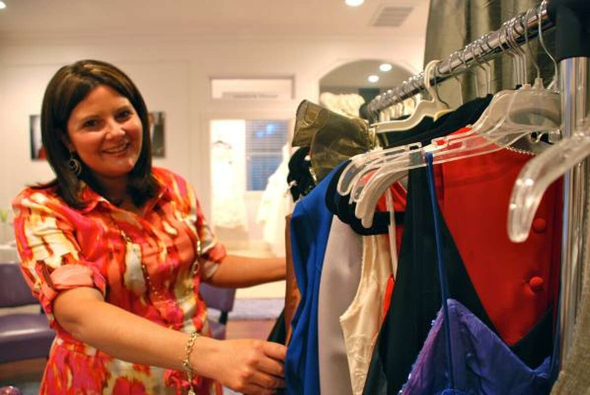 LINDSAY PEYTON: FOR THE CHRONICLE READY TO WEAR: Misty Clow, owner of Couture House Rentals in The Woodlands, shows some of the gowns she has collected for The Giving Gown Foundation.