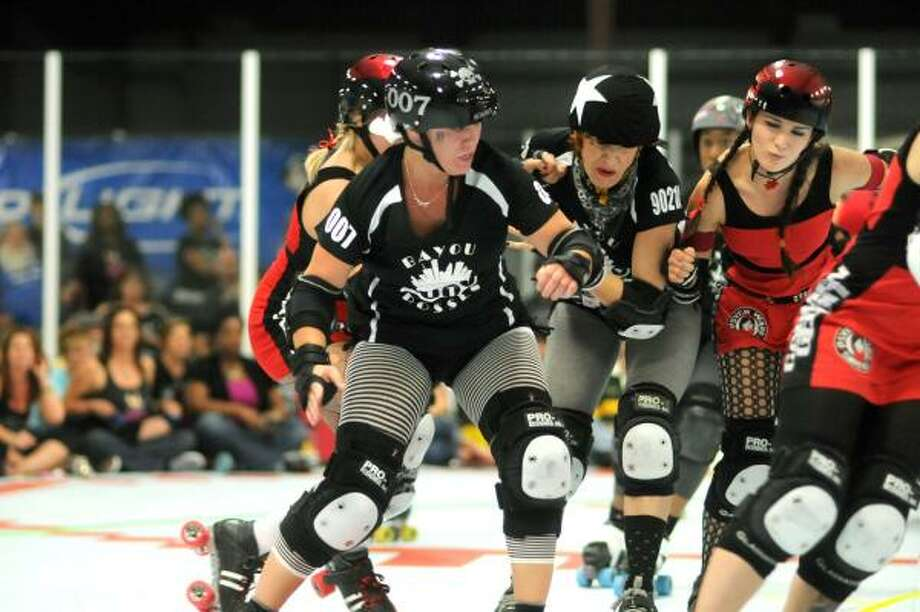 JERRY BAKER PHOTOS: FOR THE CHRONICLE MAKING A MOVE: Casey Waldner, aka Beverly Kills, center, of the Bayou City Bosses tries to work past teammate Goldie Bloxx, left, and a Psych Ward Sirens blocker during their game at the Houston Roller Derby Stadium. Photo: Jerry Baker, For The Chronicle