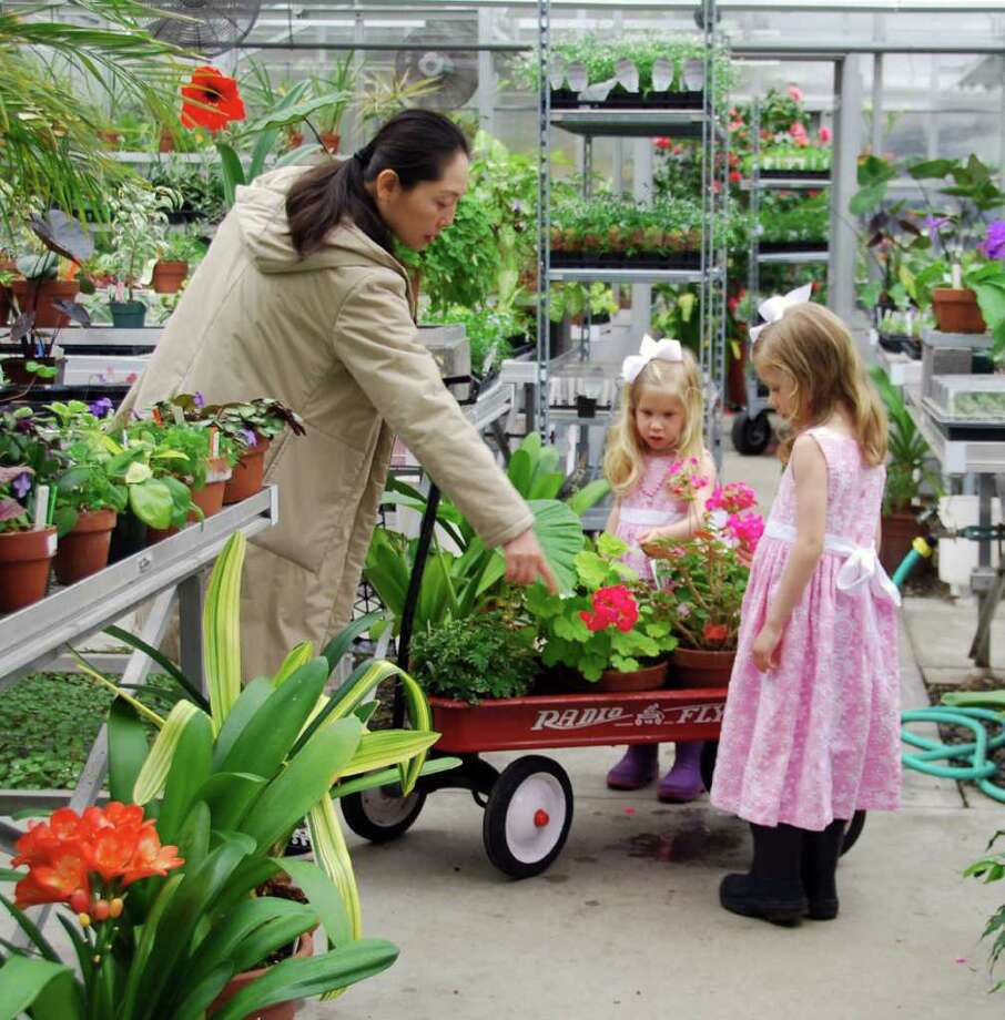 Sophia and Emilie Wasserman preview some of the Garden Education Center of Greenwich's offerings with their teacher Jing Tan Andreoli. Plants and other items will be available for sale at the center's 50th annual Gardeners' Market, Saturday, May 7, in the Montgomery Pinetum, Cos Cob. Photo: Contributed Photo / Stamford Advocate Contributed