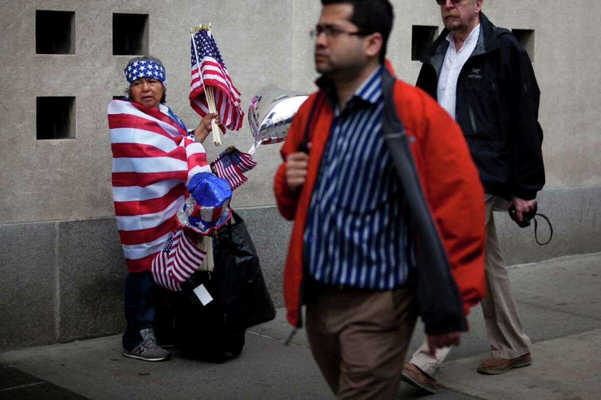 Iness Martez, left, of Newark, N.J., sells American flags at ground zero following the announcement of the death of al-Qaida leader Osama bin Laden, Monday, May 2, 2011, in New York. (AP Photo/John Minchillo)