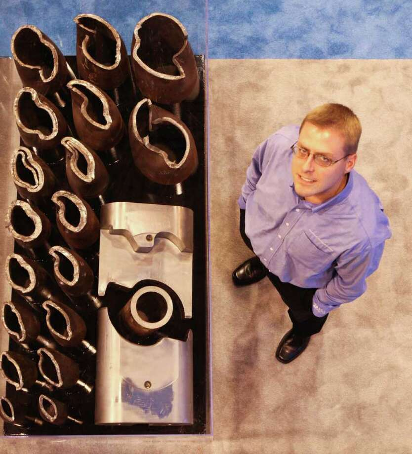 Doug Jahnke, and engineering manager wih T3 stands next to his invention the Shear All Ram during the Offshore Technology Conference Tuesday, May 3, 2011, in Reliant Center in Houston.  The SAR is attached to a Blow Out Protector and shears drilling pipe and casings. Photo: Nick De La Torre, Houston Chronicle / © 2010 Houston Chronicle