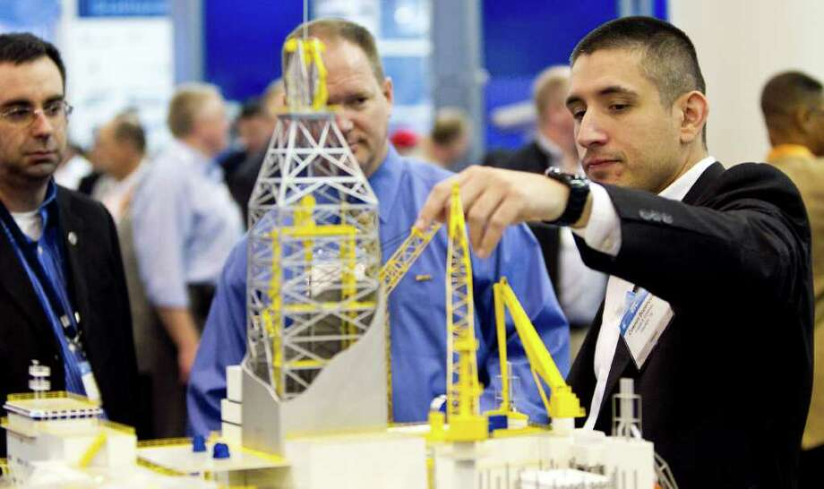 Cosmin Bozenovici A structure engineer with Friede & Goldman shows different features on a semi submersible production unit at the GVA booth on the exhibitor floor of the Offshore Technology Conference Tuesday, May 3, 2011, in Reliant Center in Houston. Photo: Nick De La Torre, Houston Chronicle / © 2010 Houston Chronicle