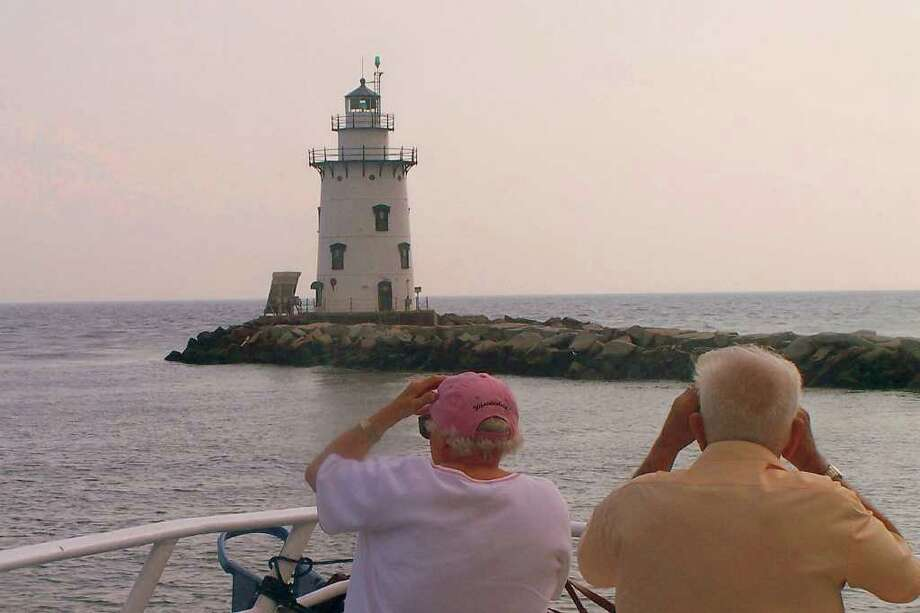 A group takes in the beauty of the Saybrook Breakwater Lighthouse in Old Saybrook during a tour of Connecticut lighthouses. Photo: Contributed Photo / Norwalk Citizen