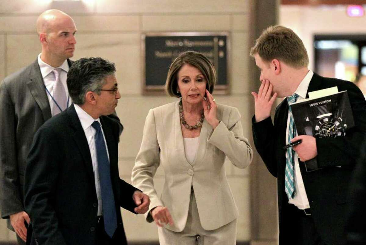 House Minority Leader Nancy Pelosi, D-Calif., is surrounded by aides and security as she leaves a closed intelligence briefing with CIA Director Leon Panetta at the Capitol in Washington, Tuesday, May 3, 2011. (AP Photo/J. Scott Applewhite)