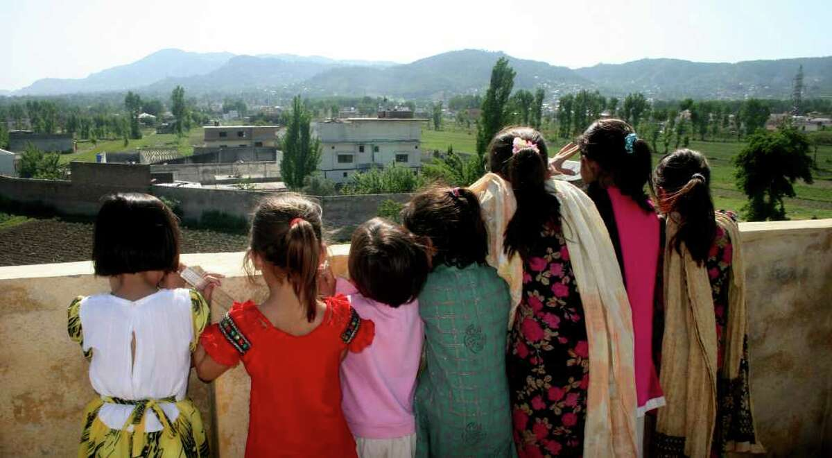 Pakistani children look out from their high vantage point, to see the compound of Osama bin Laden in Abbottabad, Pakistan, on Tuesday, May 3, 2011, after a U.S. military raid late Monday which ended with the death of the al-Qaida leader Osama bin Laden and others inside the compound. U.S. Navy SEALs swept through the compound Monday in pursuit of their target, bin Laden, and it is revealed Tuesday by White House counterterrorism adviser John Brennan that the U.S. already was scouring through items seized in the raid, said to include hard drives, DVD's, a pile of documents and other items. (AP Photo/Aqeel Ahmed)
