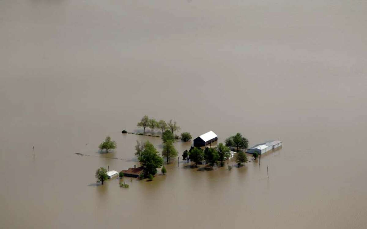 Buildings are seen surrounded by floodwater Tuesday, May 3, 2011, in Mississippi County, Mo. The Army Corps of Engineers blew a two-mile hole into the Birds Point levee in southeast Missouri, flooding 130,000 acres of farmland in Missouri's Mississippi County in an effort to protect nearby Cairo, Ill. (AP Photo/Jeff Roberson)