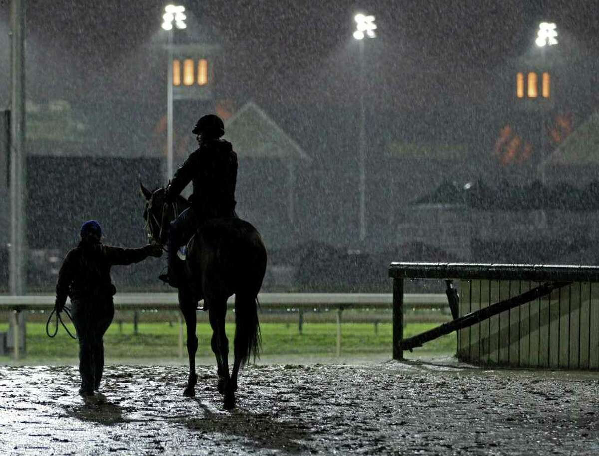 A horse is lead onto the track for a workout in the rain at Churchill Downs Tuesday, May 3, 2011, in Louisville, Ky. (AP Photo/Charlie Riedel)