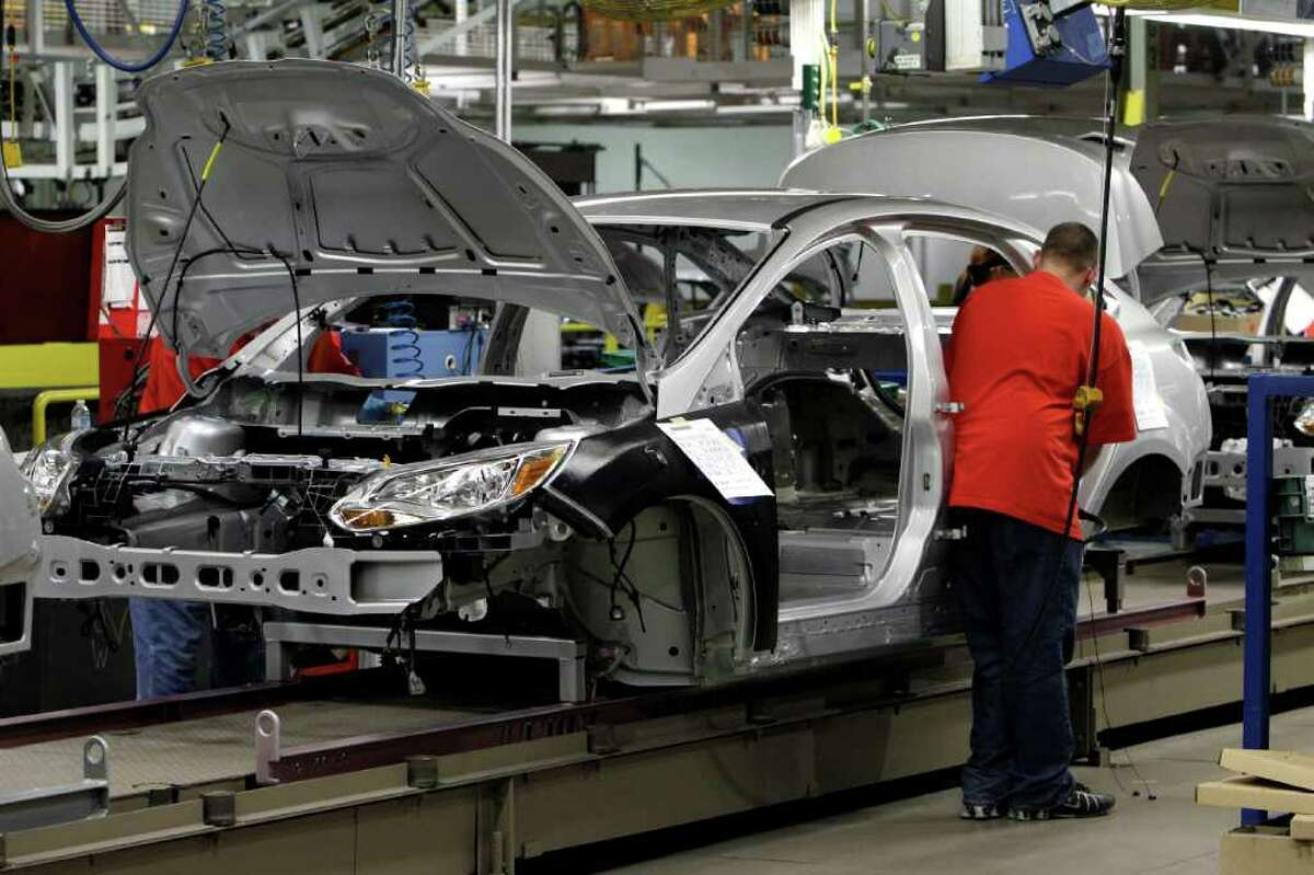 In this March 17, 2011 photo, a line worker assembles a 2012 Ford Focus at the Michigan Assembly Plant in Wayne, Mich. Businesses increased orders for industrial machinery, computers and autos in March, lifting factory orders for the fifth consecutive month. (AP Photo/Paul Sancya)