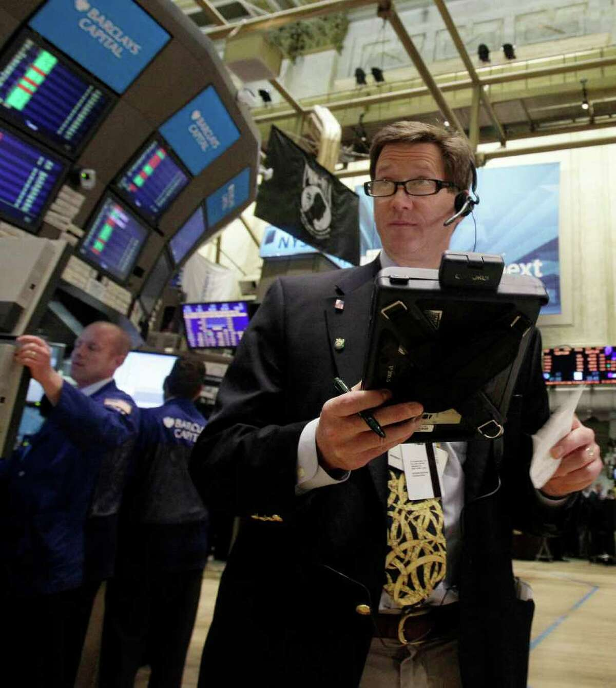 In this May 2, 2011 photo, Trader Christopher Forbes works on the floor of the New York Stock Exchange. Global stocks eased lower Tuesday as investors turned their attention toward a raft of economic news over the coming days and India's central bank lifted interest rates to keep a lid on inflation.(AP Photo/Richard Drew)