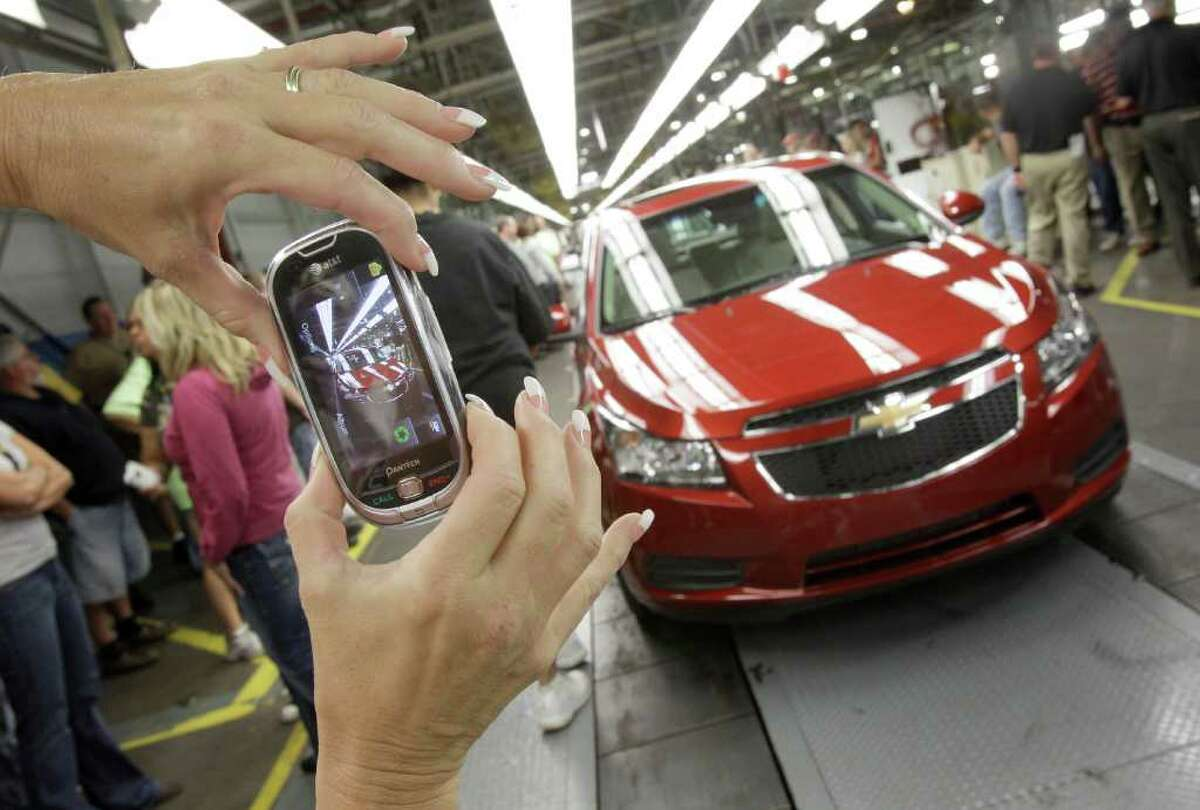 FILE - In this Sept. 8, 2010 file photo, auto worker Brenda Hedland takes a picture of the first Chevrolet Cruze compact sedan to come off the assembly line at a ceremony inside the GM factory in Lordstown, Ohio. General Motors dealers in the United States reported 232,538 total sales in April, a 26-percent increase versus April a year ago. (AP Photo/Amy Sancetta)