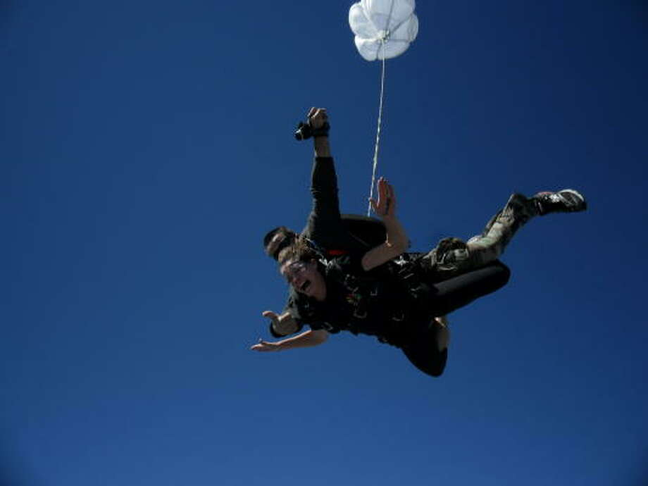 COURTESY PHOTO DOWN WE GO: Abbi Antablin, hitched to her skydiving partner, took the plunge to raise money for Opportunity International, a nonprofit organization providing assistance to developing countries. Photo: ALL