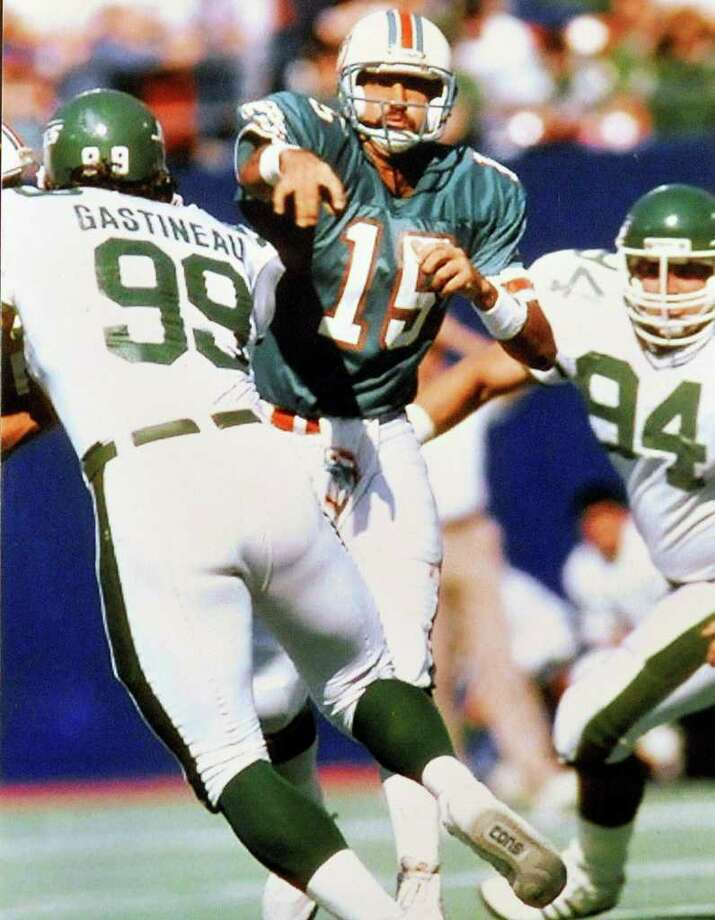 Miami Dolphin quarterback Kyle Mackey throws against the rush by NY Jets defensive end Mark Gastineau during the 1987 season. Mackey is a former National Football League player who played for the Miami Dolphins during the 1987 players strike and later played for the New York Jets.  Tuesday, April 26, 2011.  Valentino Mauricio/The Enterprise Photo: Valentino Mauricio / Beaumont