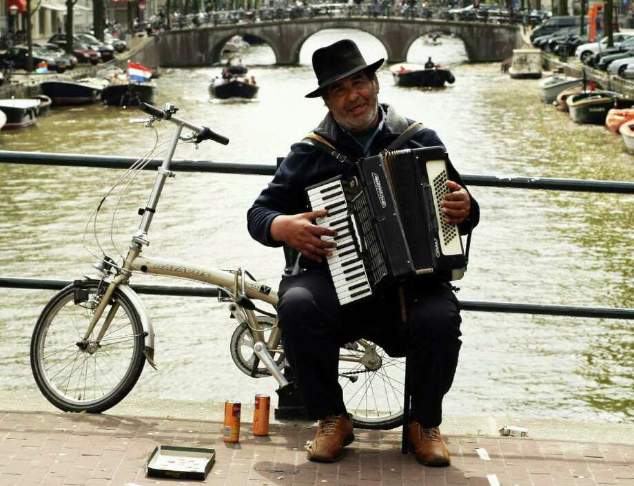 A busker performs from the seat of his bike on a canal on May 11, 2009 in Amsterdam, Netherlands. The 750,000 people who live in Amsterdam own more than 600,000 bicycles. Photo: Mark Dadswell, Getty Images / 2009 Getty Images