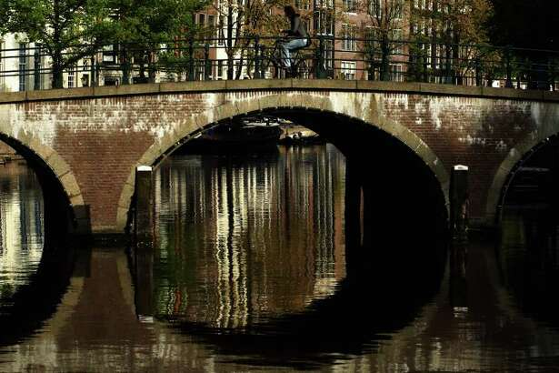 AMSTERDAM, NETHERLANDS - MAY 11:  A cyclist makes his way across a canal on May 11, 2009 in Amsterdam, Netherlands. The 750,000 people who live in Amsterdam own over 600,000 bicycles.
