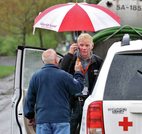 Schuylerville Mayor John Sherman, left, holds an umbrella for Red Cross volunteer Chuck Allen as they conduct a damage assessment on Schuyler Island after the Hudson River once again flooded low-lying areas in Schuylerville on Wednesday, May 4, 2011.  (John Carl D'Annibale / Times Union) Photo: John Carl D'Annibale / 00013036A