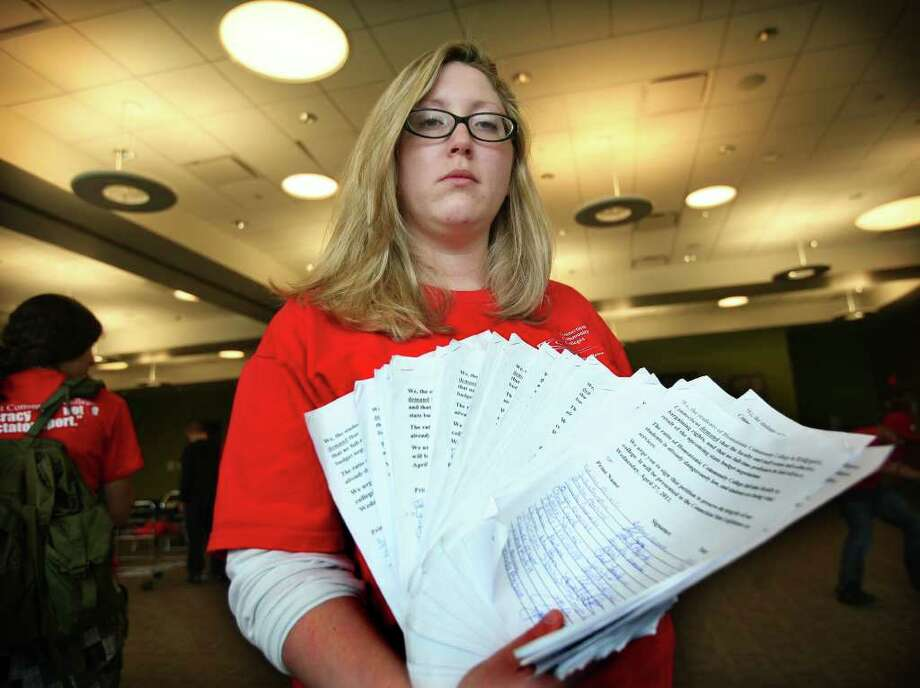 Kaitlyn Shake of Fairfield, a student at Housatonic Community College in Bridgeport, shows petitions containing about two thousand signatures that she collected from students to protest state budget cuts that would layoff professors at her school. Shake spoke to students at the Bridgeport school on Wednesday, May 4, 2011. Photo: Brian A. Pounds / Connecticut Post