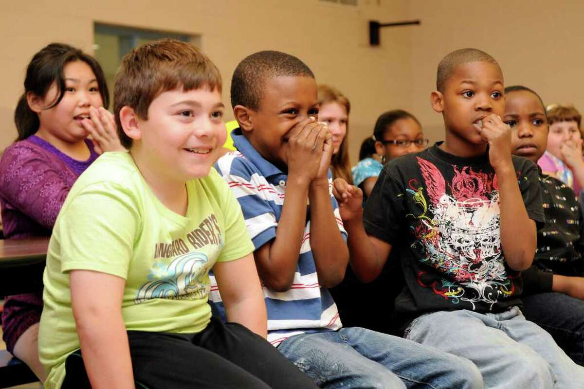 Jalani Taylor, 10, center, grins with pride as he recognizes the poem being read aloud is his work -- signifying he had won a poetry contest at Westover Elementary School in Stamford, CT on Wednesday, May 4, 2011. Classmates Joey Belmonte, 9 1/2, (left) and Angelo Nicholas, 10, listen to the reading. Third and fourth graders had written poems for their mothers in honor of mother's day, and Nagi Osta, president of Nagi Jewelers of Stamford, hands out awards for the top three poems.