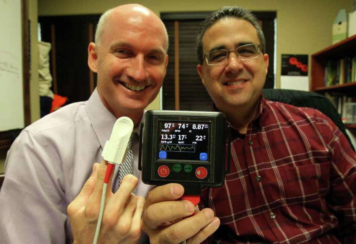 David Spencer (left), President and CEO of Speer Medical Devices, Inc. and Anthony Catalano (right) the company's Chief Technology Officer are working to produce a device (center, foreground) that can be used by military combat medics in the field that takes vital signs and is non-invasive. The device will check hemoglobin levels and check pulse oxygenation and is small and light in weight. (Monday May 2, 2011) JOHN DAVENPORT/jdavenport@express-news.net
