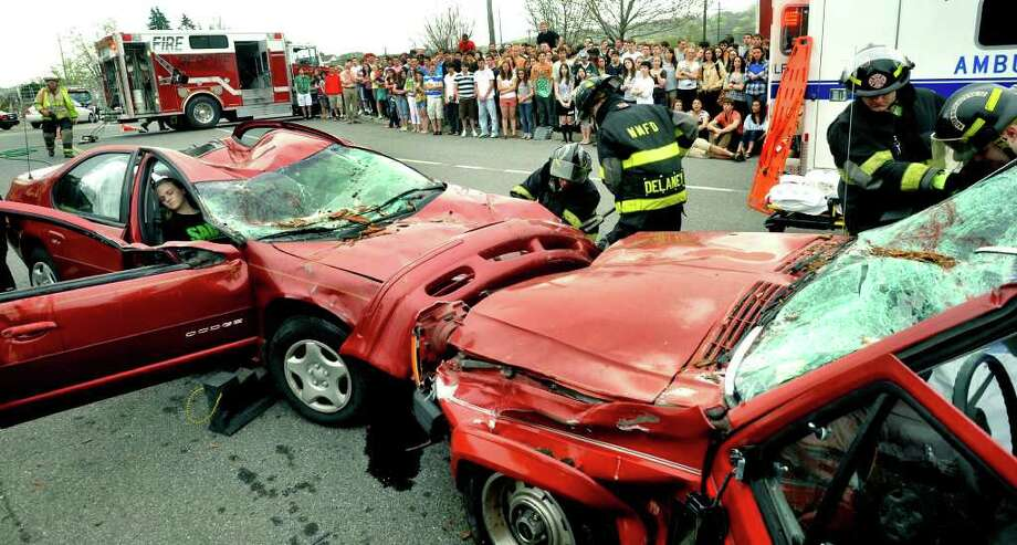 SPECTRUM/First responders, including New Milford Ambulance, fire and rescue emergenc personnel, tend to the scene of a mock crash staged April 28, 2011 at New Milford High School by Students Against Destructive Decisions. Photo: Michael Duffy / The News-Times