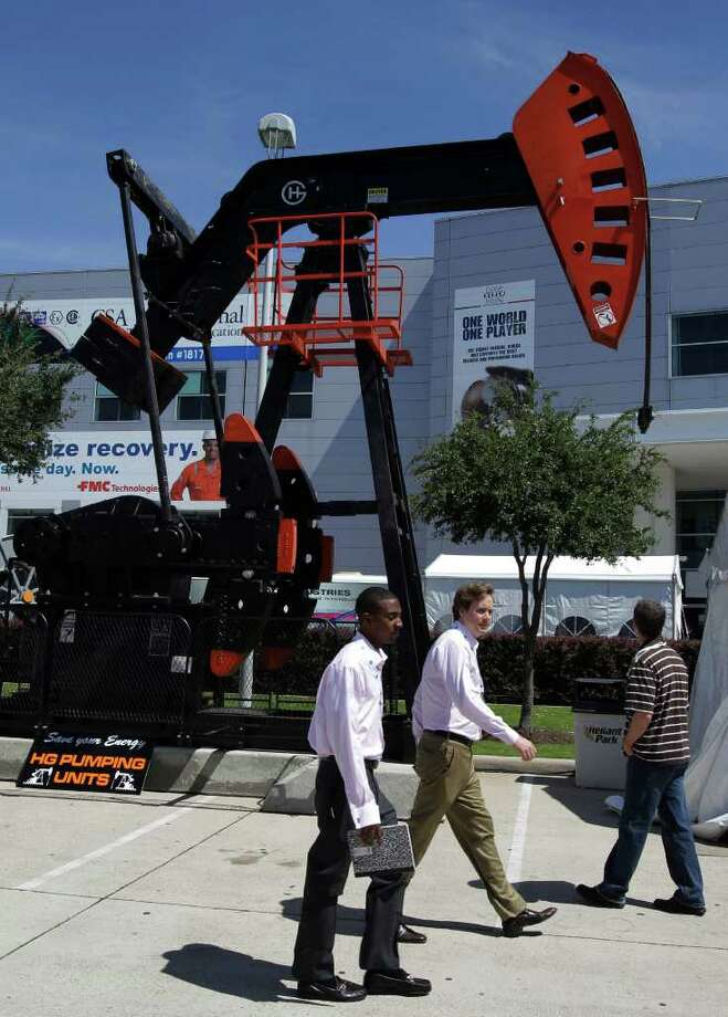 Visitors walk pas a pumping unit at the annual Offshore Technology Conference Wednesday, May 4, 2011, in Houston. More than 65,000 people and 2,000 exhibitors representing more than 110 countries attend the four day conference. Photo: Pat Sullivan, AP / AP