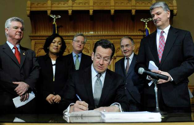 Connecticut Gov. Dannel P. Malloy signs a two-year $40.1 billion budget bill into law as Speaker of the House Christopher Donovan, D-,Meriden, left, State Sen. Toni Harp, D-New Haven, second from left, House Majority Leader Brendan Sharkey D-Hamden, behind left, Sen Majority Leader Martin Looney, D-New Haven, behind right, Senate President Donald Williams Jr., D-Brooklyn, right, look on, at the Capitol in Hartford, Conn., Wednesday, May 4, 2011.  (AP Photo/Jessica Hill) Photo: Jessica Hill, AP / AP2011