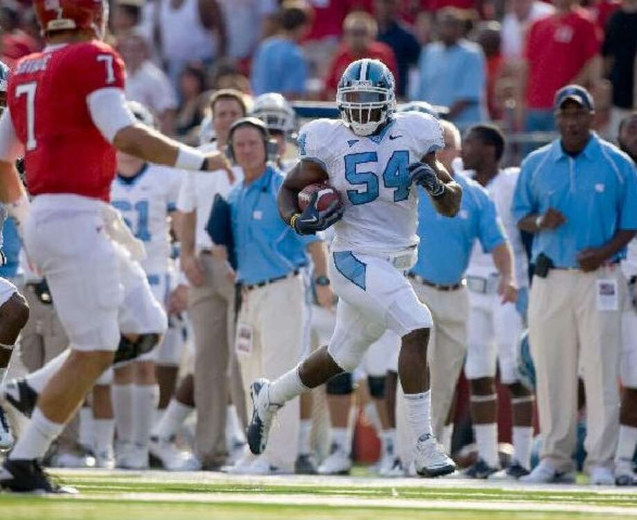 Bruce Carter, returning an interception 55 yards against Rutgers, tore his ACL in November and likely won't be full speed for training camp. ROBERT WILLETT/MCCLATCHY