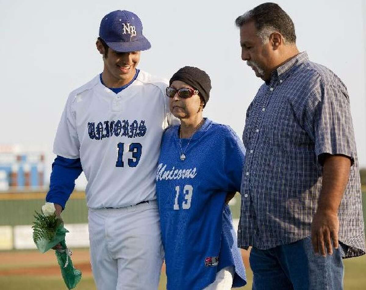 Lupita Garza walks with her son Ralph Jr. (left) and husband Ralph Sr. during a parents' night ceremony before New Braunfels played Judson on Friday. Lupita, who has multiple myeloma, was released from the hospital last week and was determined to see Ralph Jr. play for the Unicorns. DARREN ABATE/SPECIAL TO THE EXPRESS-NEWS