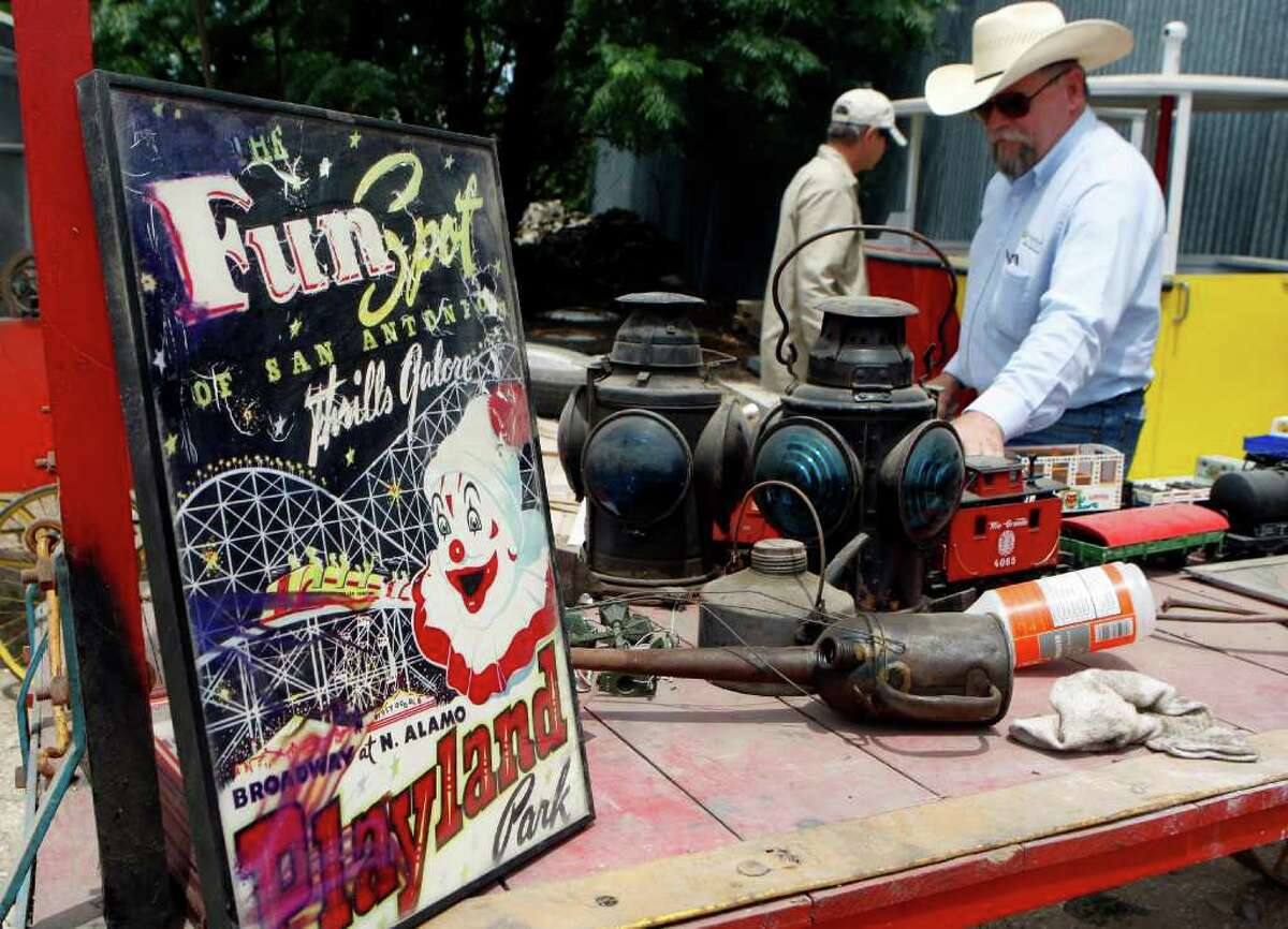 Auctioneer Randall Hill, wearing cowboy hat, looks over items to be auctioned Friday. The collection includes the framed poster from Playland Park and memorabilia from Fiesta celebrations. Also, the auction will feature the gondolas that were part of the sky ride that used to take viewers high above Brackenridge Park.