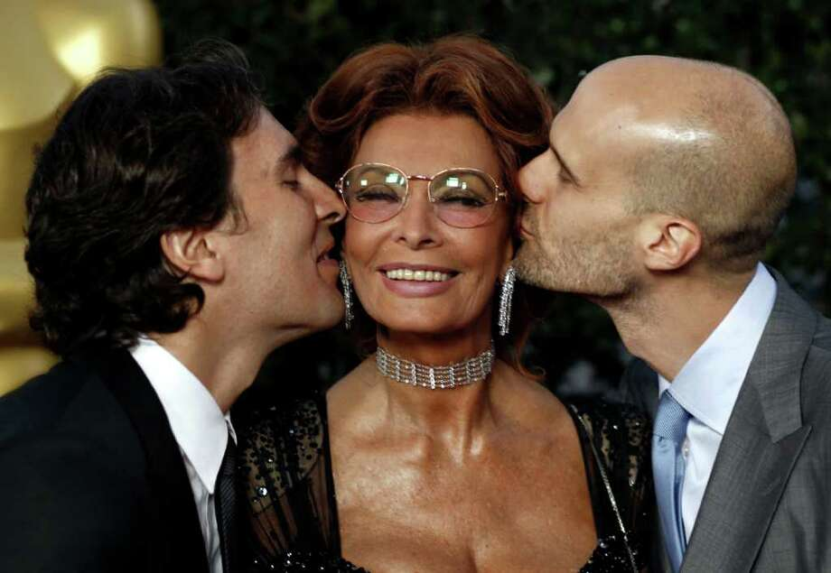 Actress Sophia Loren, center, gets a kiss from her sons, Carlo Ponti Jr., left, and Edoardo Ponti at The Academy of Motion Picture Arts and Sciences Tribute honoring her in Beverly Hills, Calif., Wednesday, May 4, 2011.  Loren's life and career will be celebrated by friends and colleagues Wednesday. Photo: AP