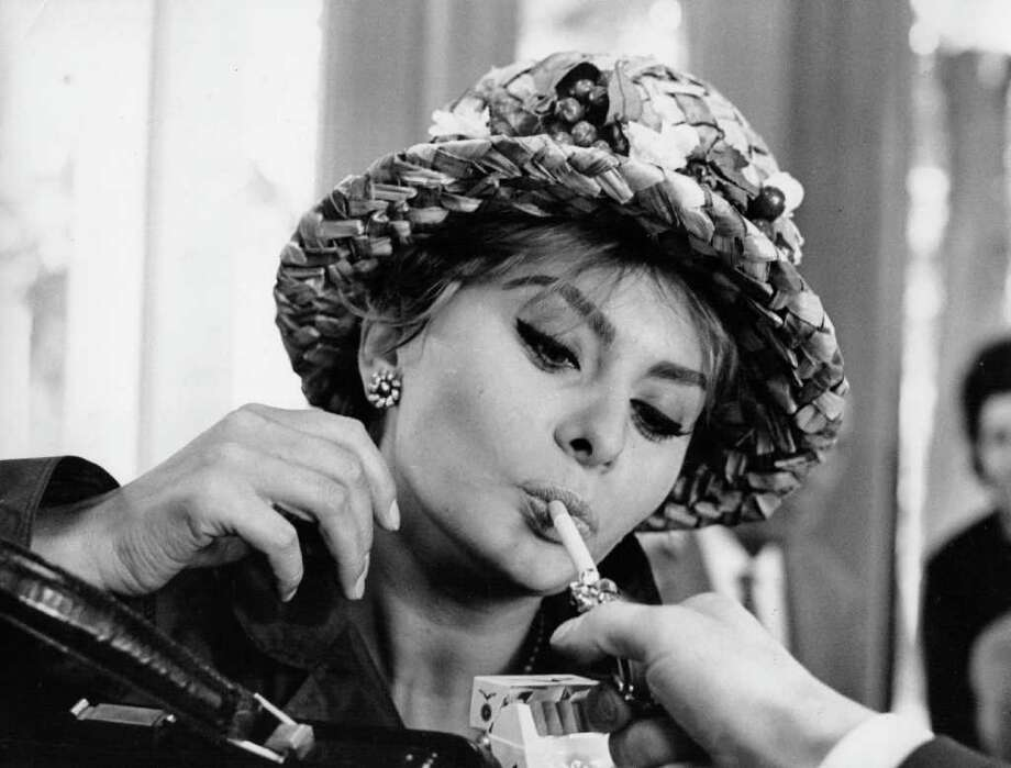 April 1961: Italian actress Sophia Loren accepting a light at the Turin flower show. Photo: Keystone Features, Getty Images / Hulton Archive