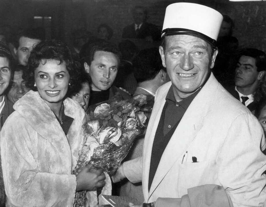 "ROME, ITALY - MARCH 7:  American actor John Wayne (R) and Italian actress Sophia Loren (L) arrive at Rome from Africa after the broken leg of Wayne during the shooting of ""The Legend of the Lost"". Photo: STAFF, AFP/Getty Images / AFP"