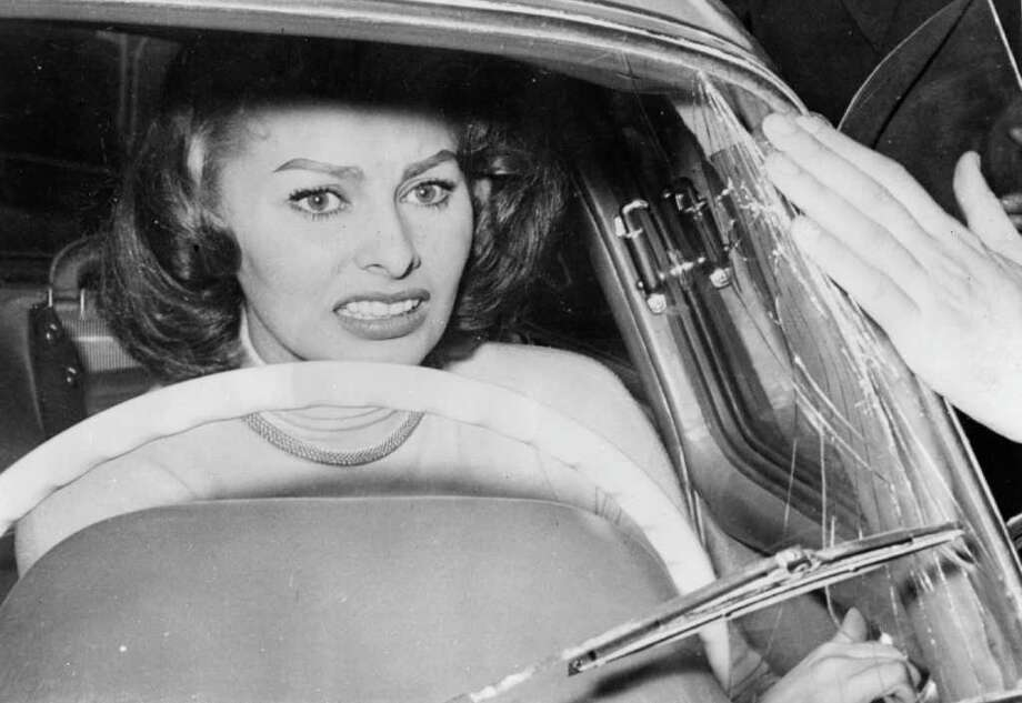 9th April 1956:  Italian film star Sophia Loren cowers in her car as a crowd of ardent fans press around her, smashing the windscreen in their eagerness to see her. Sophia is taking part in the annual Rome to San Remo Cinema Car Rally. Photo: Keystone, Getty Images / Hulton Archive