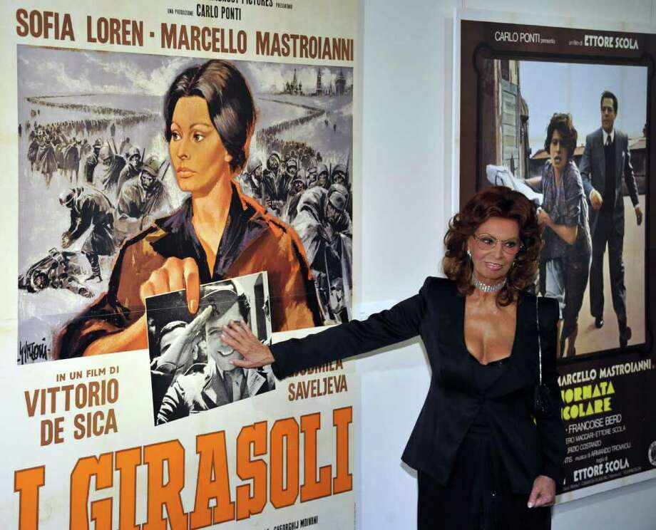 "Italian actress Sophia Loren covers the face of her old co-star Marcello Mastroianni as she poses by a poster for her 1970 film Sunflower, or in Italian ""I Girasoli"", during her visit to the Italian Culture Centre in Tokyo on October 14, 2010. Italian movie star was awarded the Japan Art Association's Praemium Imperiale, one of the most lucrative prizes in the arts world, in the theatre and film category on October 13.   AFP PHOTO / Yoshikazu TSUNO Photo: YOSHIKAZU TSUNO, AFP/Getty Images / 2010 AFP"