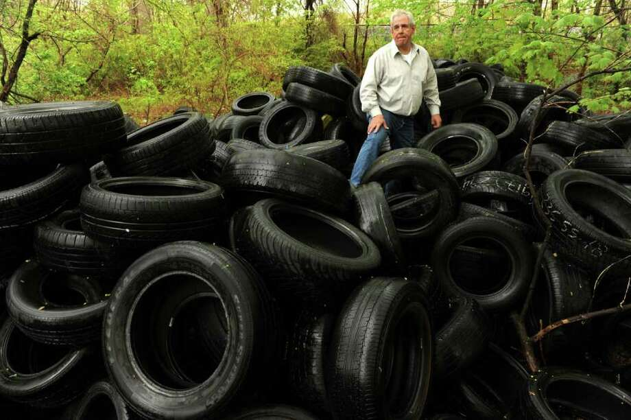 In a May 4, 2011 photo, Norwich Blight/Code Enforcement Officer Ed Martin climbs through a pile of tires dumped on Norwich City property behind the Dairy Queen on Route 12 in the Taftville section of Norwich, looking for a company name so he can track where the tires originated.  Martin thinks probably a business hired someone to remove the tires and then they were just dumped. Martin said there are approximately 2,500 tires that were dumped Monday night.  (AP Photo/The Day, Dana Jensen)   MANDATORY CREDIT:  DANA JENSEN/THE DAY, MAGS OUT, TV OUT, INTERNET OUT, NO SALES Photo: Dana Jensen, AP / The Day Publishing Company