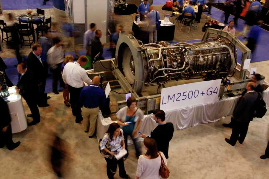 An Offshore Technology Conference (OTC) attendees get a look at a gas turbine at the GE Oil & Gas booth in Reliant Center Wednesday, May 4, 2011, in Houston.  The OTC runs through tomorrow. Photo: Johnny Hanson, Chronicle / © 2011 Houston Chronicle