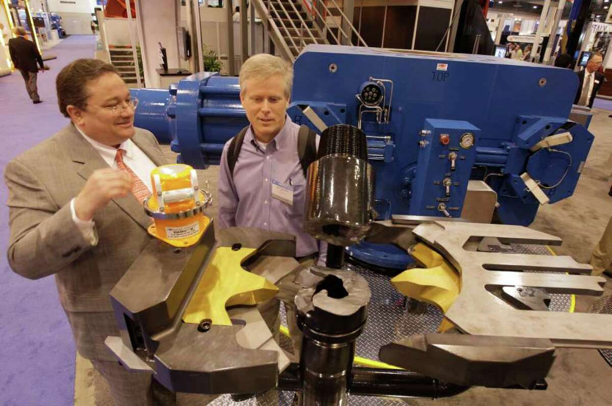 Trey Mebane, National Oilwell Varco director of business development , left, talks with Carl Lawrence, right, of Houston during the Offshore Technology Conference at Reliant Center Thursday, May 5, 2011, in Houston. They are standing behind a ShearMax, a low force casing shear rams. Shown top of the ShearMax is a Blackbox Downhole Dynamics Recorder (yellow light) and behind them is a blow out preventer.