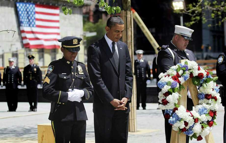 NEW YORK, NY - MAY 05:  U.S. President Barack Obama (C) bows his head during a moment of silence with 9-11 first responders New York Police Department officer Stephanie Moses (L) and a firefighter during a wreath laying ceremony at Ground Zero after Osama bin Laden was killed on May 5, 2011 in New York City. Obama also visited a New York Fire Department firehouse and met with families of victims of the terrorist attack on September 11, 2001during his visit to New York.   (Photo by Mario Tama/Getty Images) *** Local Caption *** Barack Obama; Photo: Mario Tama, Getty Images / 2011 Getty Images