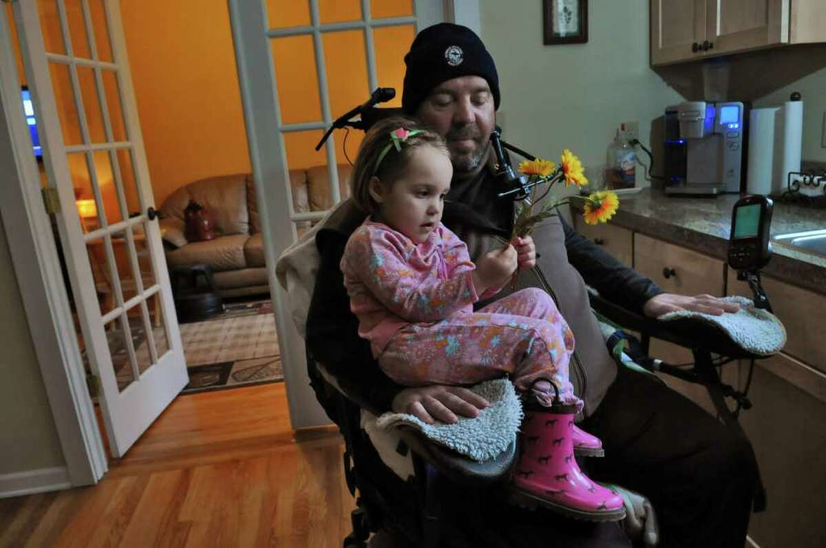 Michael Jones, a recreational rugby player who was paralyzed in February 2010, spends some time with his daughter Liliana, 3, in the kitchen of their home on Wednesday May 4, 2011 in Delmar, NY. ( Philip Kamrass / Times Union )