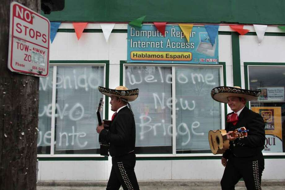 Members of Mariachi Ayutla walk past a sign welcoming a new bridge to the South Park neighborhood during a celebration kicking off construction for a replacement for its closed thouroughfare on Thursday, May 5, 2011 in Seattle's South Park neighborhood. Photo: JOSHUA TRUJILLO / SEATTLEPI.COM