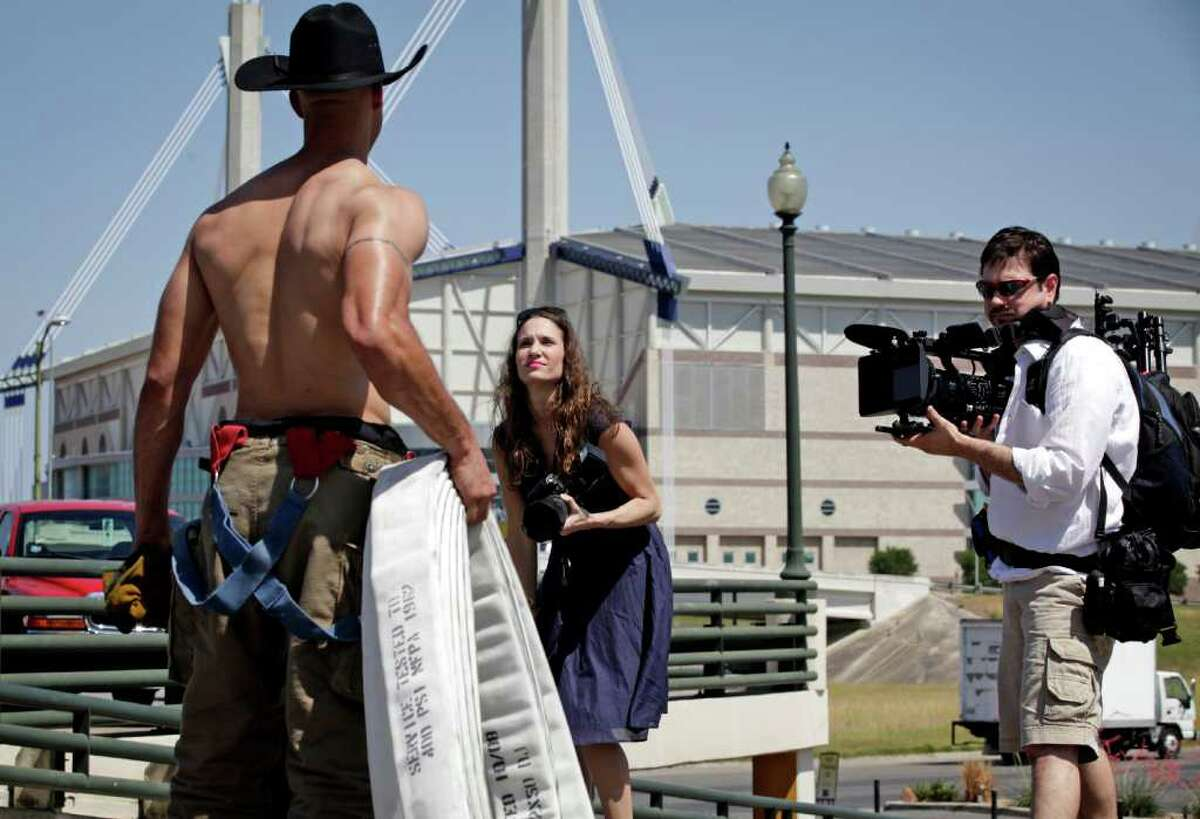 Katherine Kostreva (center) photographs San Antonio firefighter Thaddeus Anwar (left) in HemisFair Park for a national firefighters calendar to be published in August.