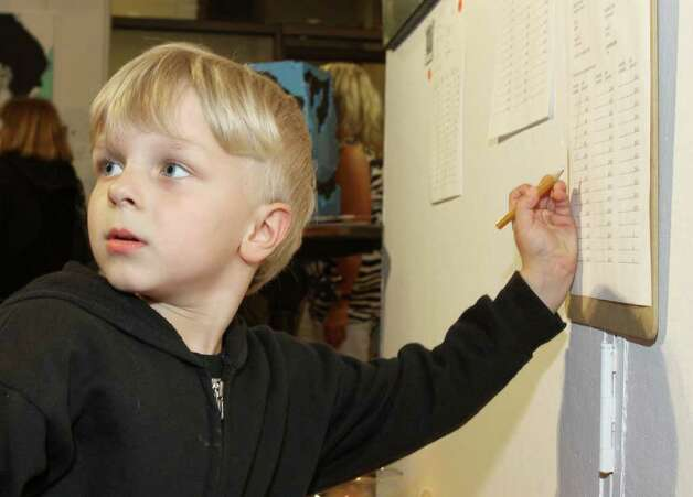 "Four-year-old art lover Maceo Pray asks his mom ""How do I make a six?"" so he could write her bidder number on the bid sheet during Knock It Off!, a benefit for Albany Center Gallery. Albany, NY - April 29, 2011 - (Photo by Joe Putrock / Special to the Times Union) Photo: Joe Putrock / Joe Putrock"