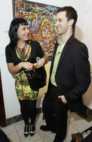 Contributing artist Sarah Petrucci, left, and Trevor Ehmann stand in front of her painting during Knock It Off!, a benefit for Albany Center Gallery. Albany, NY - April 29, 2011 - (Photo by Joe Putrock / Special to the Times Union) Photo: Joe Putrock / Joe Putrock