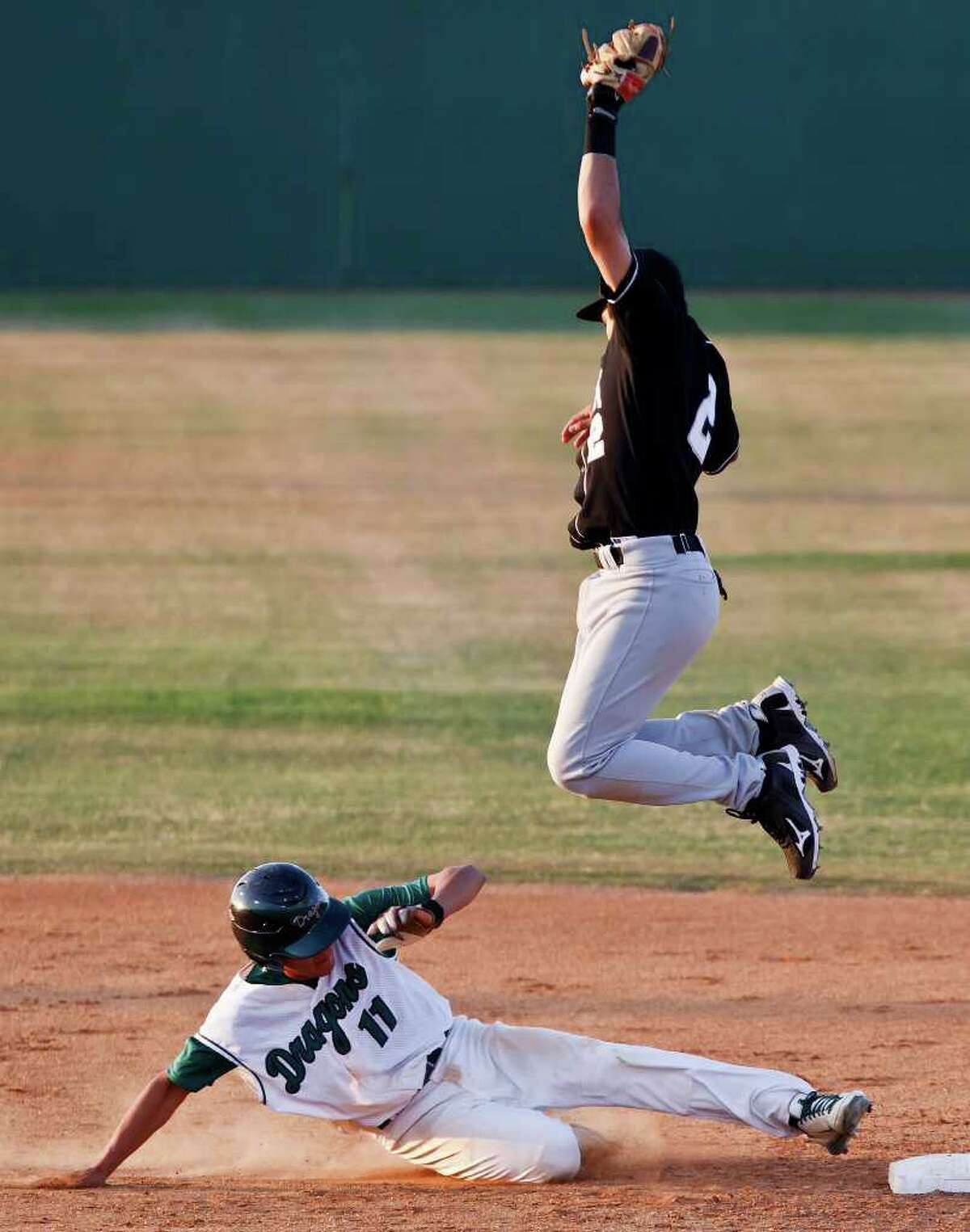Clark shortstop Jason Cervantes leaps high into the air to catch a throw from third base as Southwest's Edgar Vaszuez slides safely back to second base during the Cougar's 3-2 first round playoff victory over the Dragons at Northside Field #2 on May 5, 2011. MARVIN PFEIFFER/mpfeiffer@express-news.net