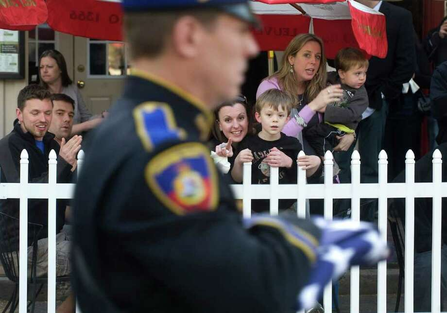 Cody Baker, 4 of Stamford, watches as his uncle marches with the Stamford police officers and other officers throughout Connecticut and several other states as they participate in the Stamford Police Memorial Parade in honor of National Police Week in Stamford, Conn. on Saturday May 6, 2011. The parade honors Connecticut officers killed in the line of duty. Photo: Kathleen O'Rourke, Stamford Advocate / Stamford Advocate